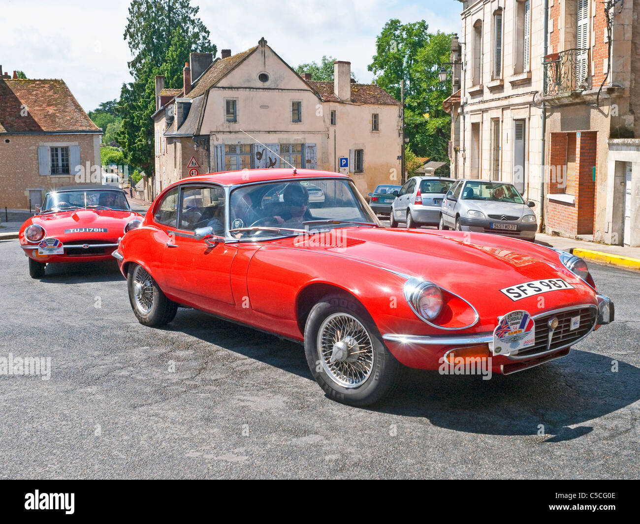 Two red E-Type Jaguar sports cars in town - France. - Stock Image