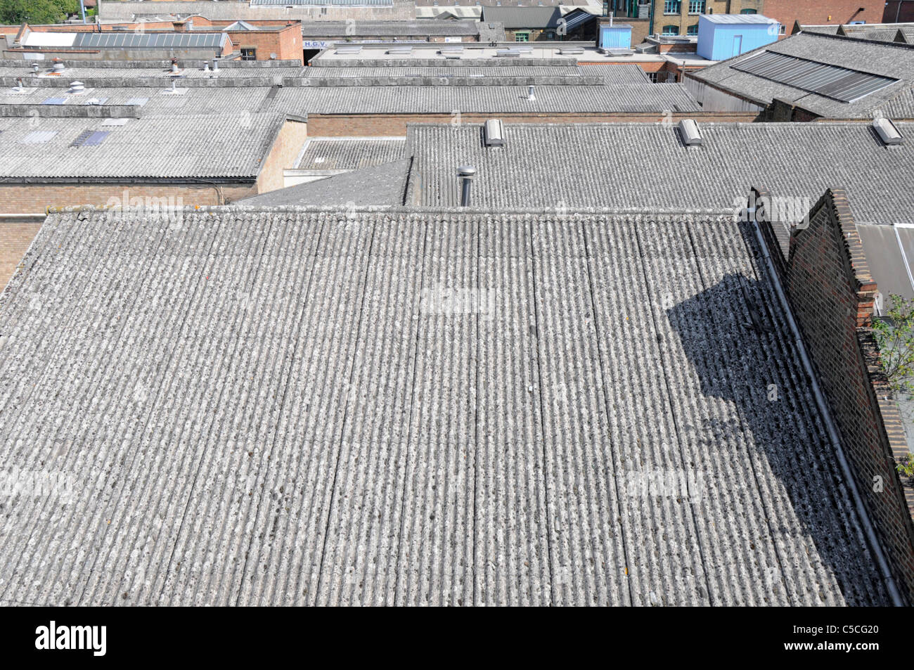 Corrugated asbestos roofing on industrial units - Stock Image