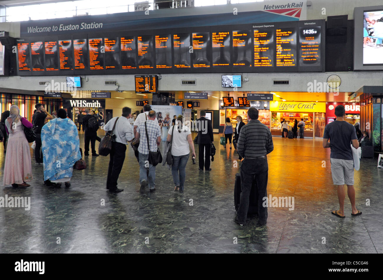 Euston train station concourse travellers viewing train departure board London England UK - Stock Image