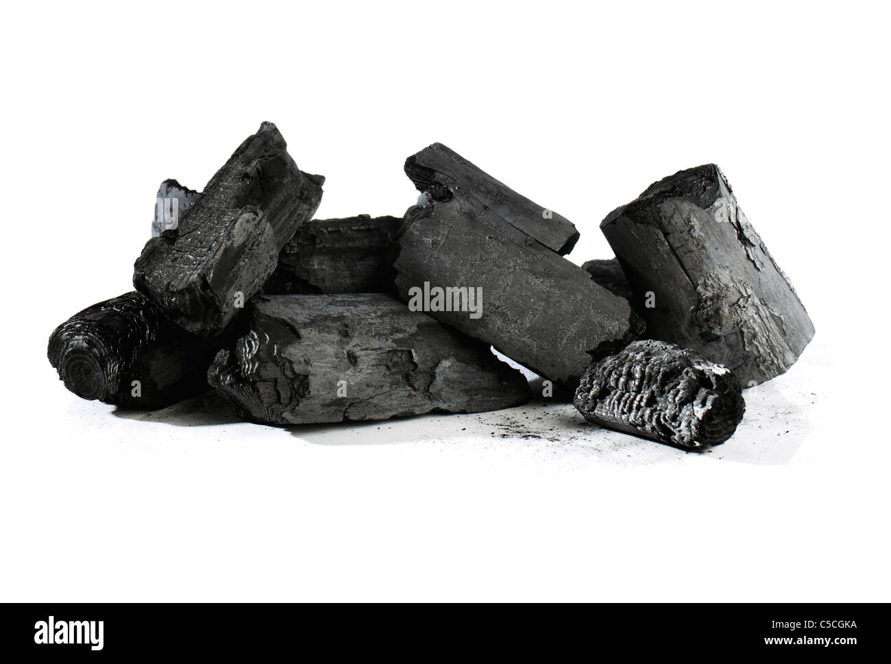 Lumps of black charcoal on white - Stock Image