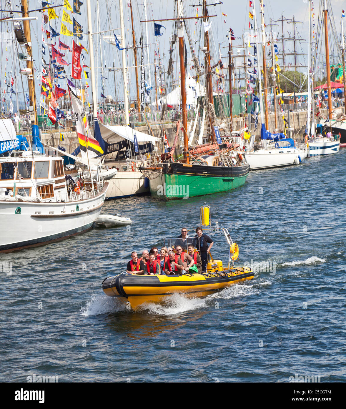 Passengers on a Rigid Inflatable Boat (RIB) pass between the sailing ships in the Tall Ships Race 2011 at Greenock, - Stock Image