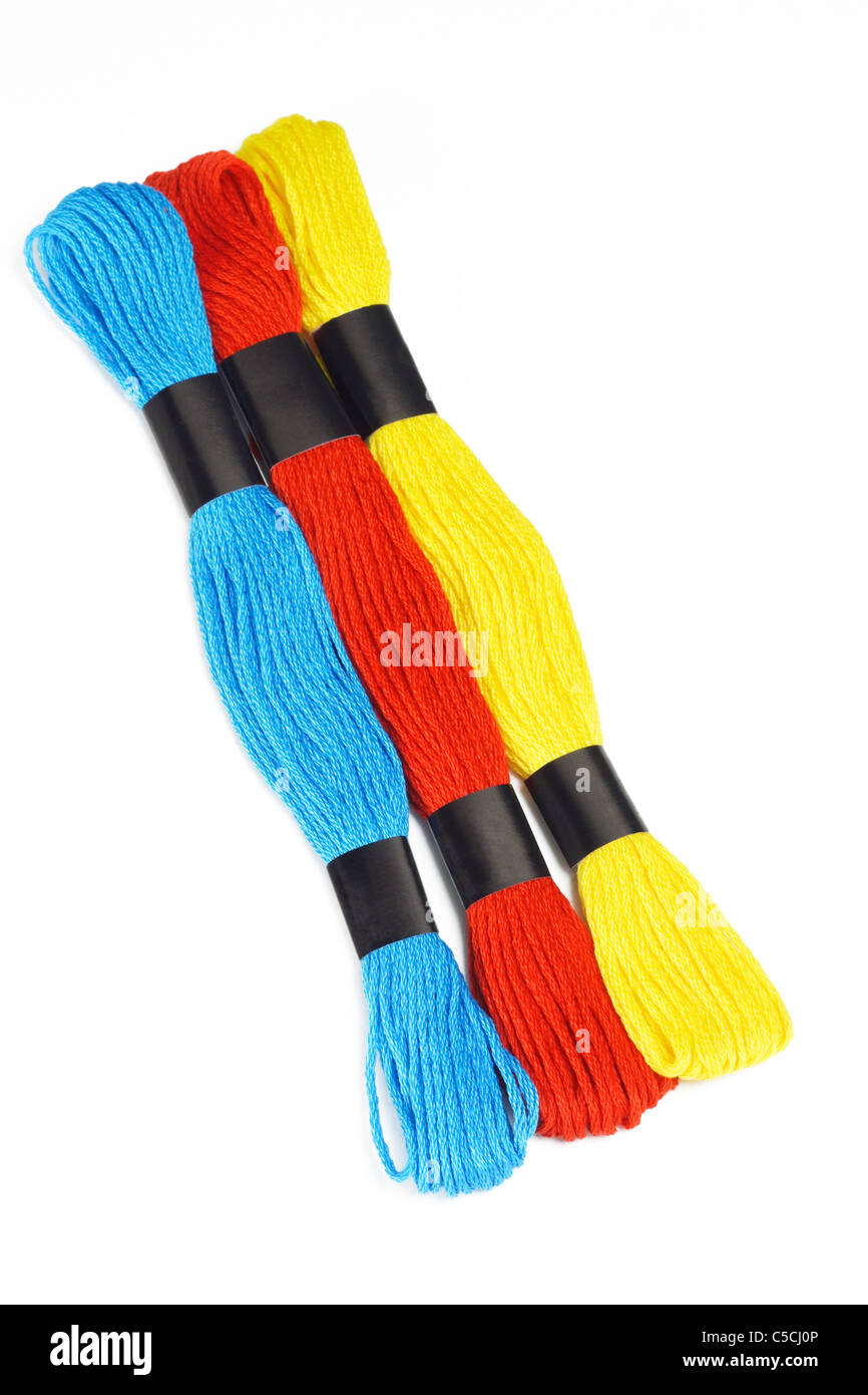 Three colorful embroidery threads on white background - Stock Image