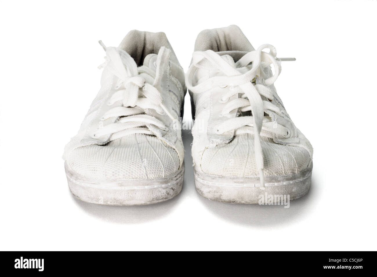 old worn out school canvas shoes on white background - Stock Image