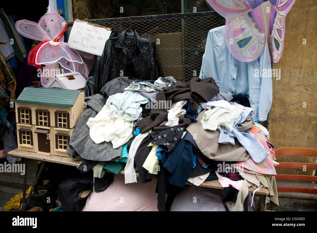 Old clothes and jumble outside charity shop, Walcot, Bath, England - Stock Image