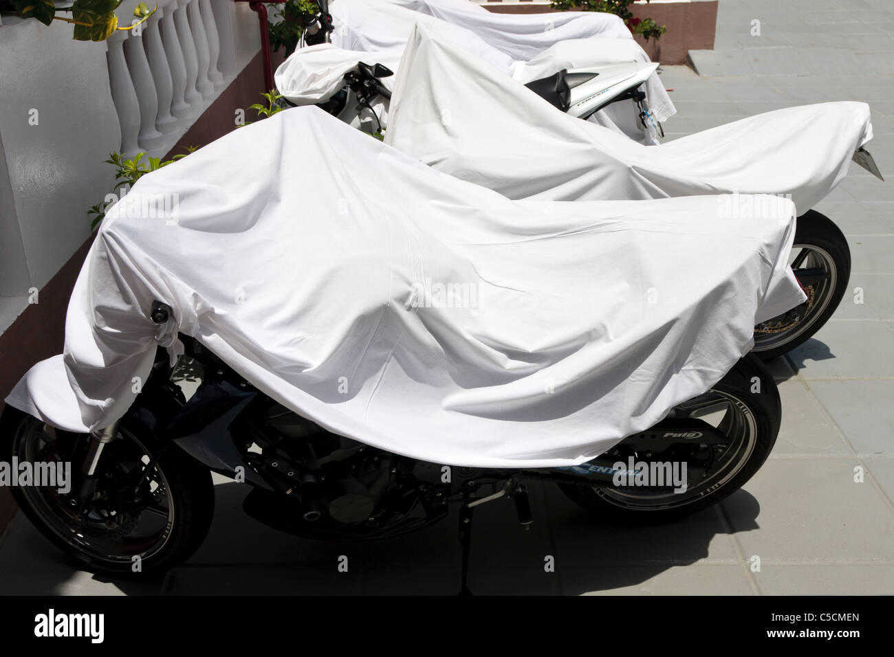 Sheets thrown over motorcycles to keep them cool in the hot summer sun outside an apartment block in Valle Gran - Stock Image