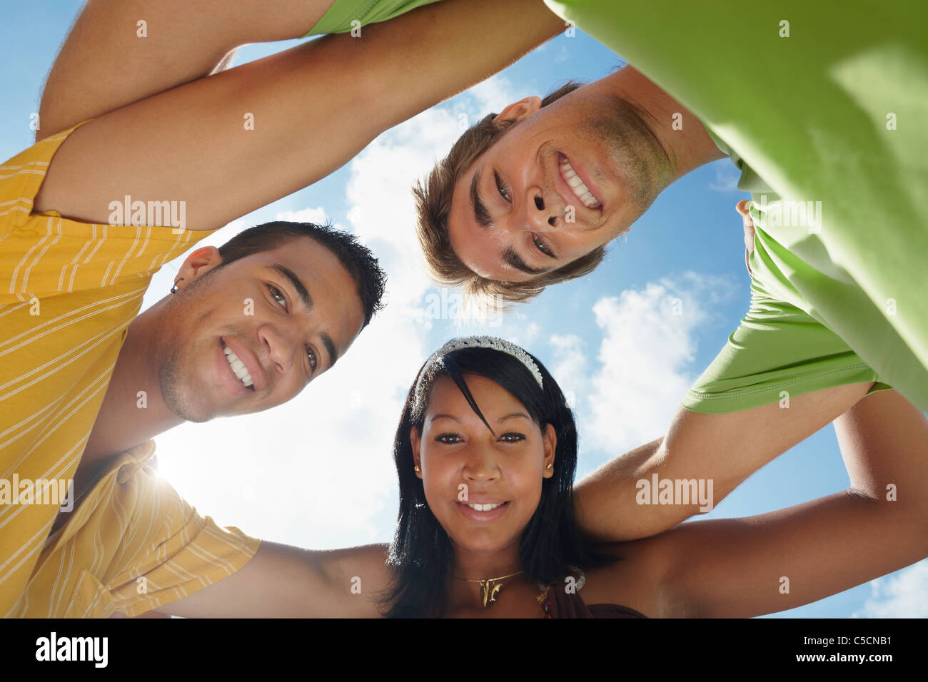 multiethnic group of male and female friends hugging and looking at camera with sky in background. Low angle view - Stock Image