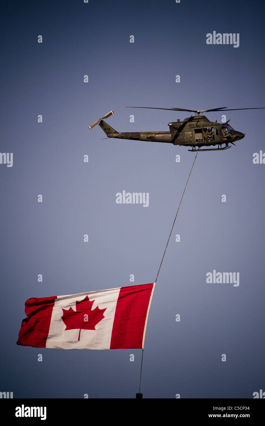 Canadian military helicopter flying national flag during Calgary Stampede Week - Stock Image
