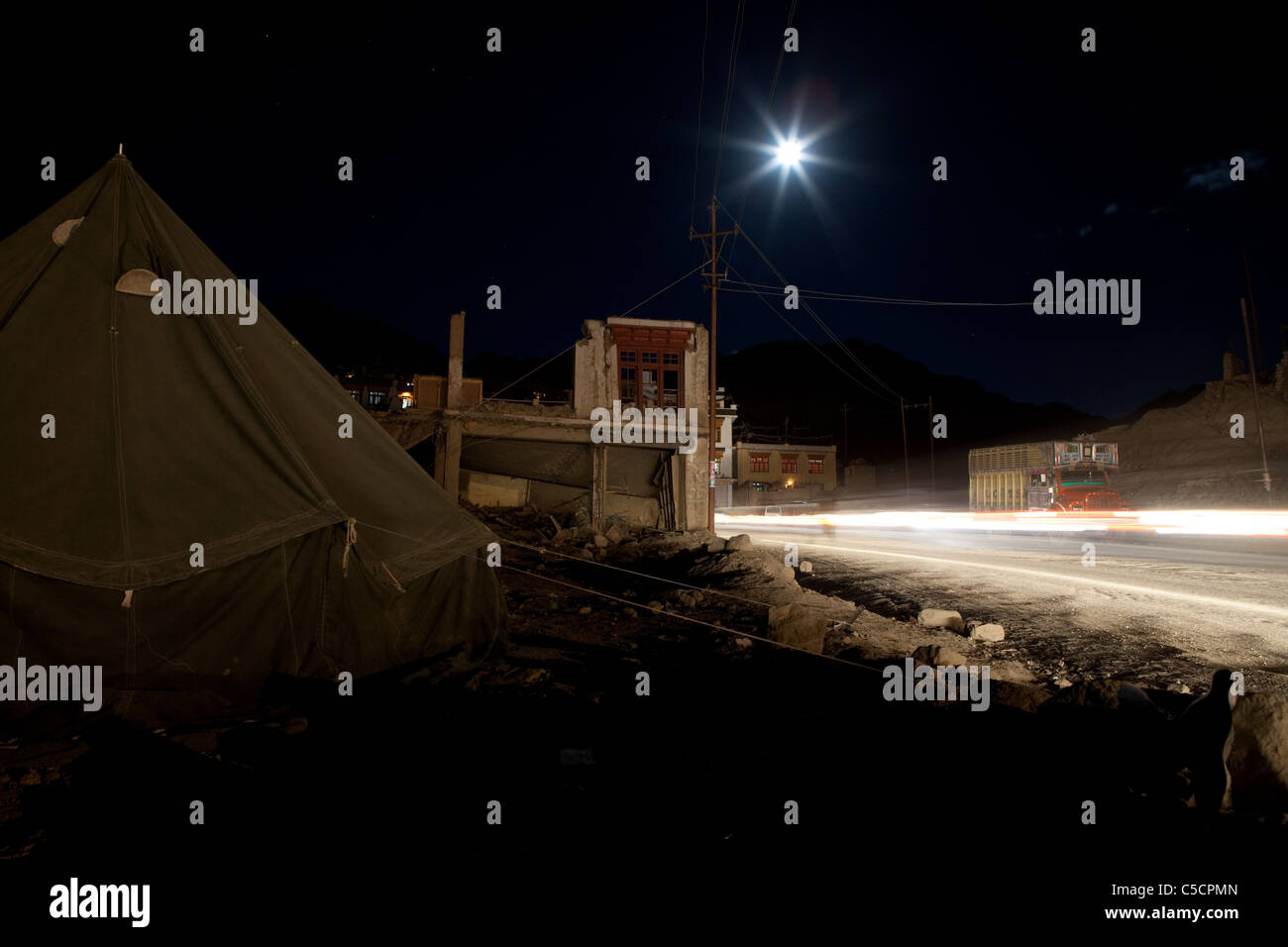 Ruined house near the bus-stop in Leh with full moon above. - Stock Image