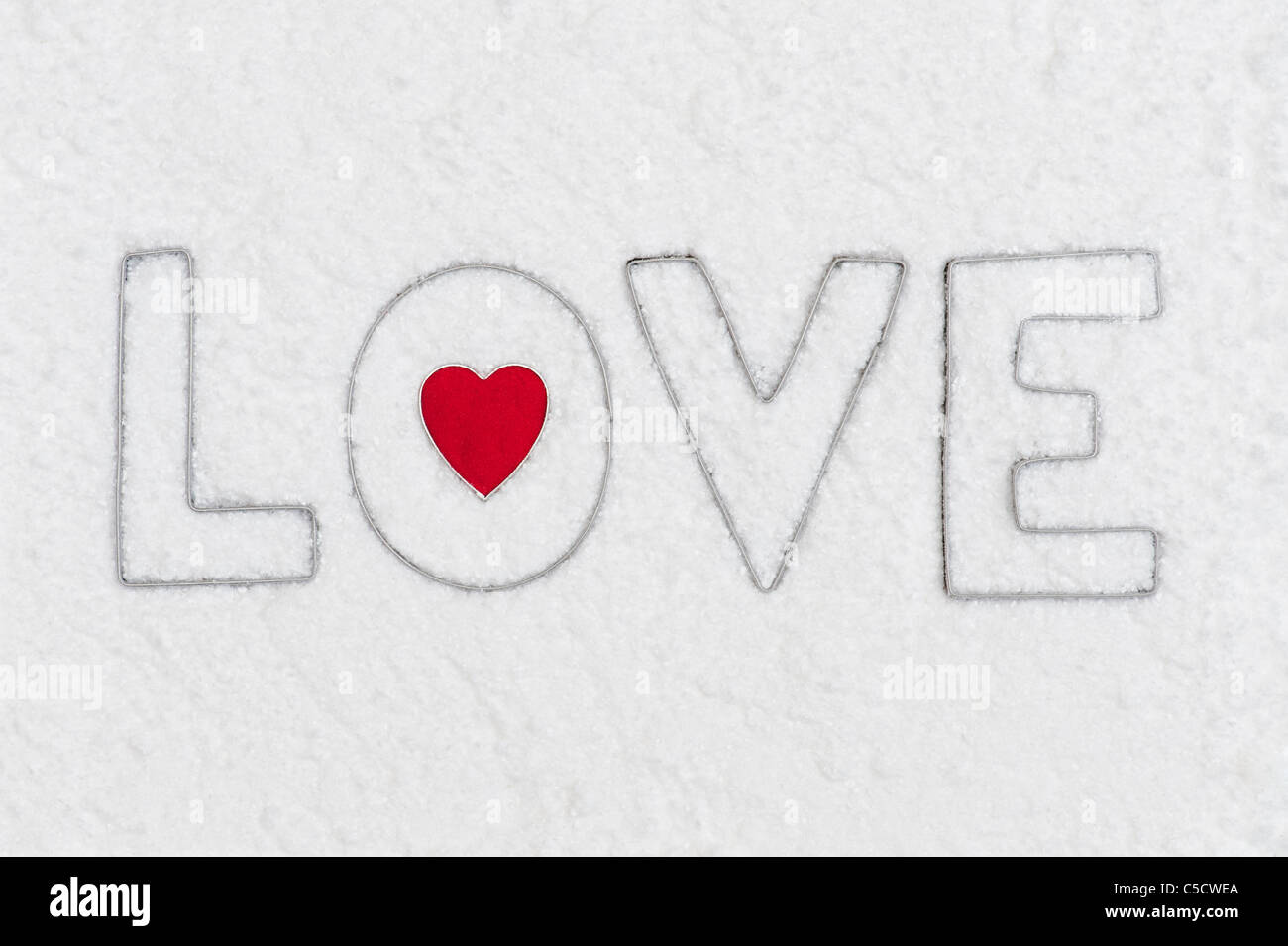 LOVE and heart shape metal letters in snow - Stock Image