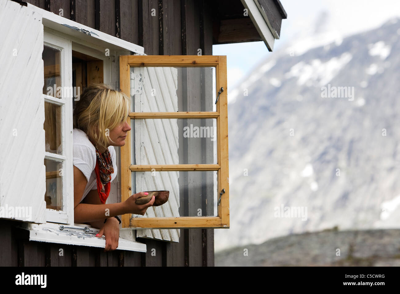 Blond woman with a kuksa looking through windows against blurred mountain - Stock Image