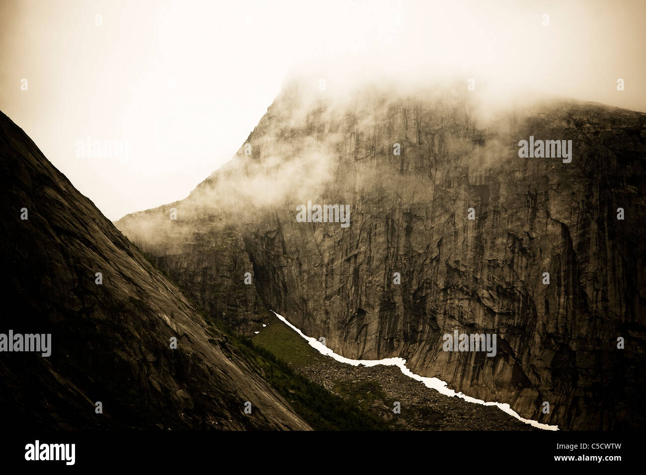 Scenic view of rock walls along steep in fog - Stock Image