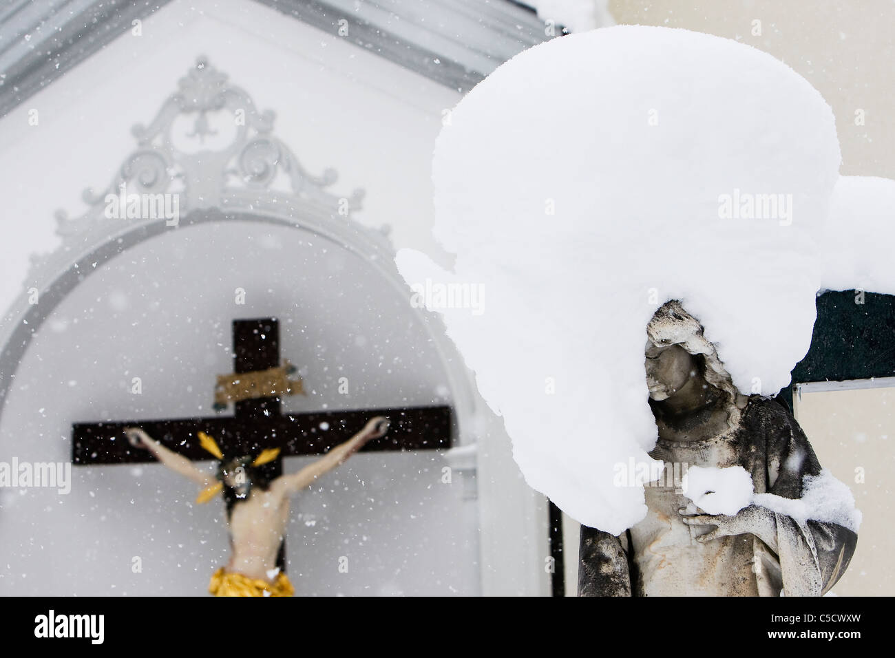 Abandoned over snowing patron saint by cross at Switzerland - Stock Image