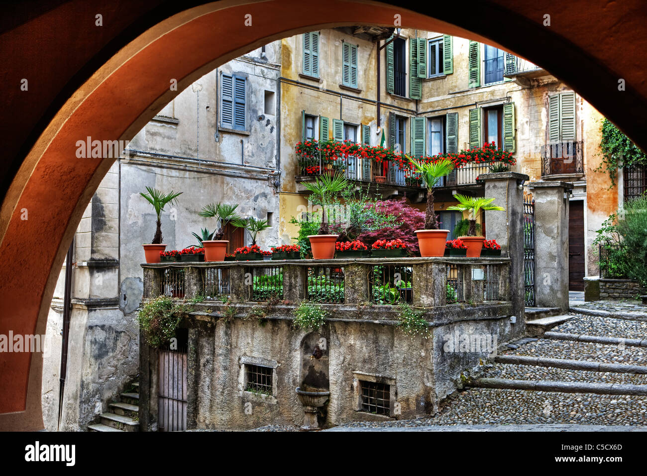 Looking through an arch in old houses in the town of Orta in Piedmont, Italy - Stock Image