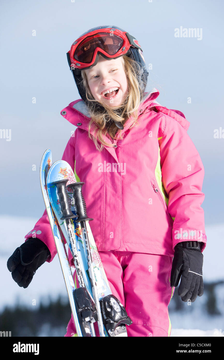 Portrait of a little happy girl in pink skiwear - Stock Image