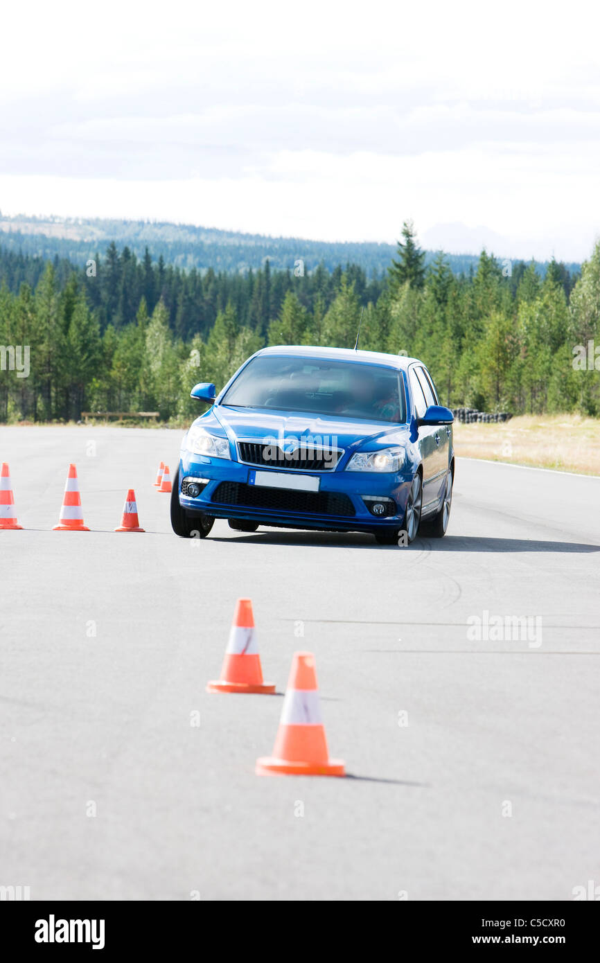 Blue car on asphalt road along traffic cones and against trees - Stock Image