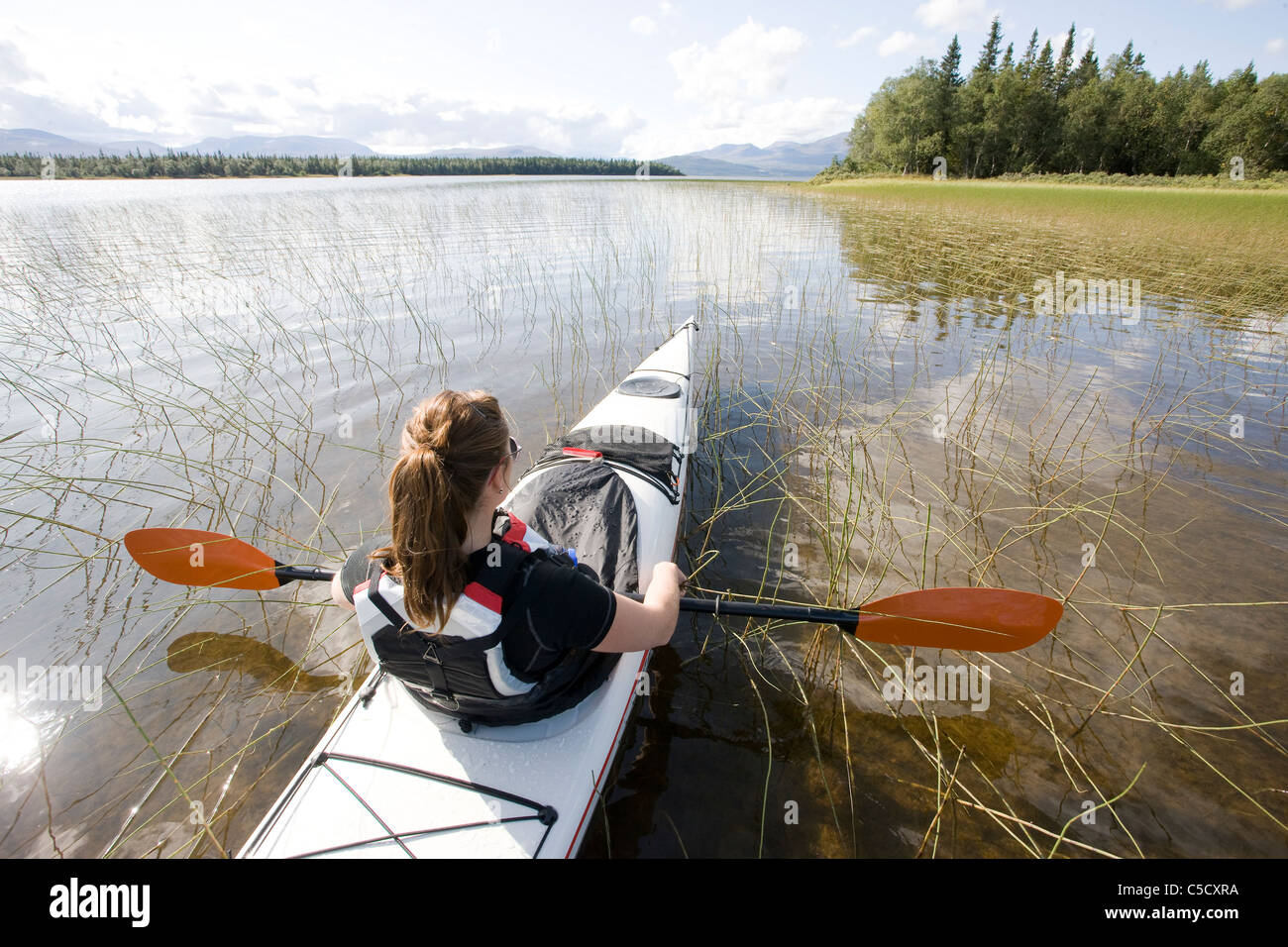 Rear view of a woman kayaking in the peaceful lake - Stock Image