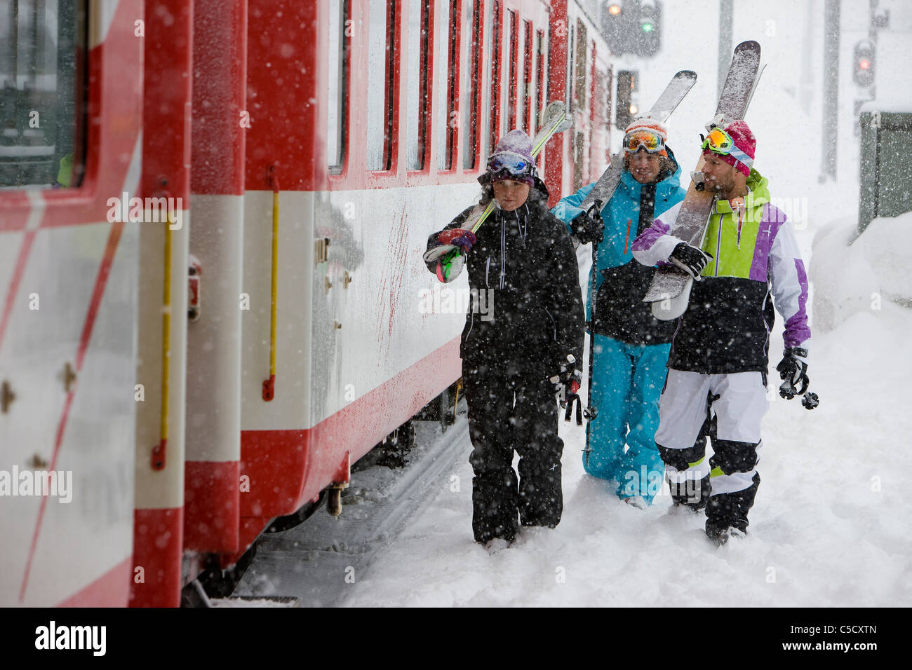 Skiers with skis on shoulders by the train on railway station platform on a snowy day at Switzerland - Stock Image