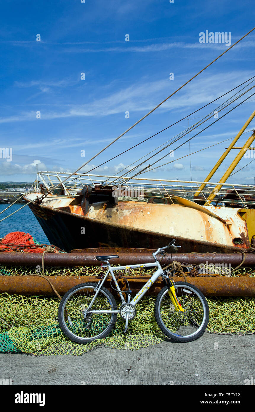 A bicycle leaning against fishing nets in Newlyn Harbour. - Stock Image
