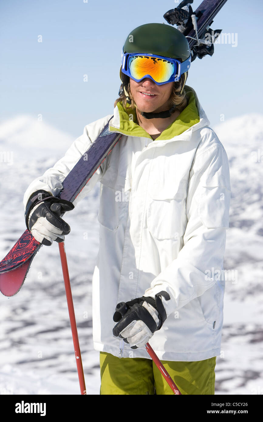 59ce3781c98 Portrait of a male skier with ski goggles and ski on shoulder - Stock Image