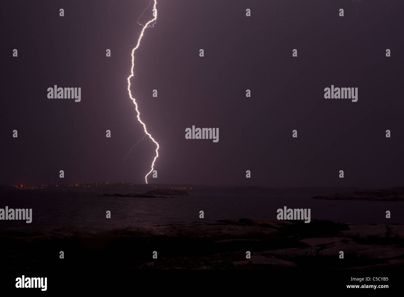 Scenic shot of lightning storm over the peaceful sea in the evening Stock Photo