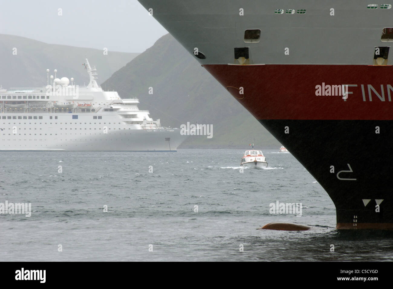 Close-up of a cropped nautical vessel in water with a ship in the background - Stock Image