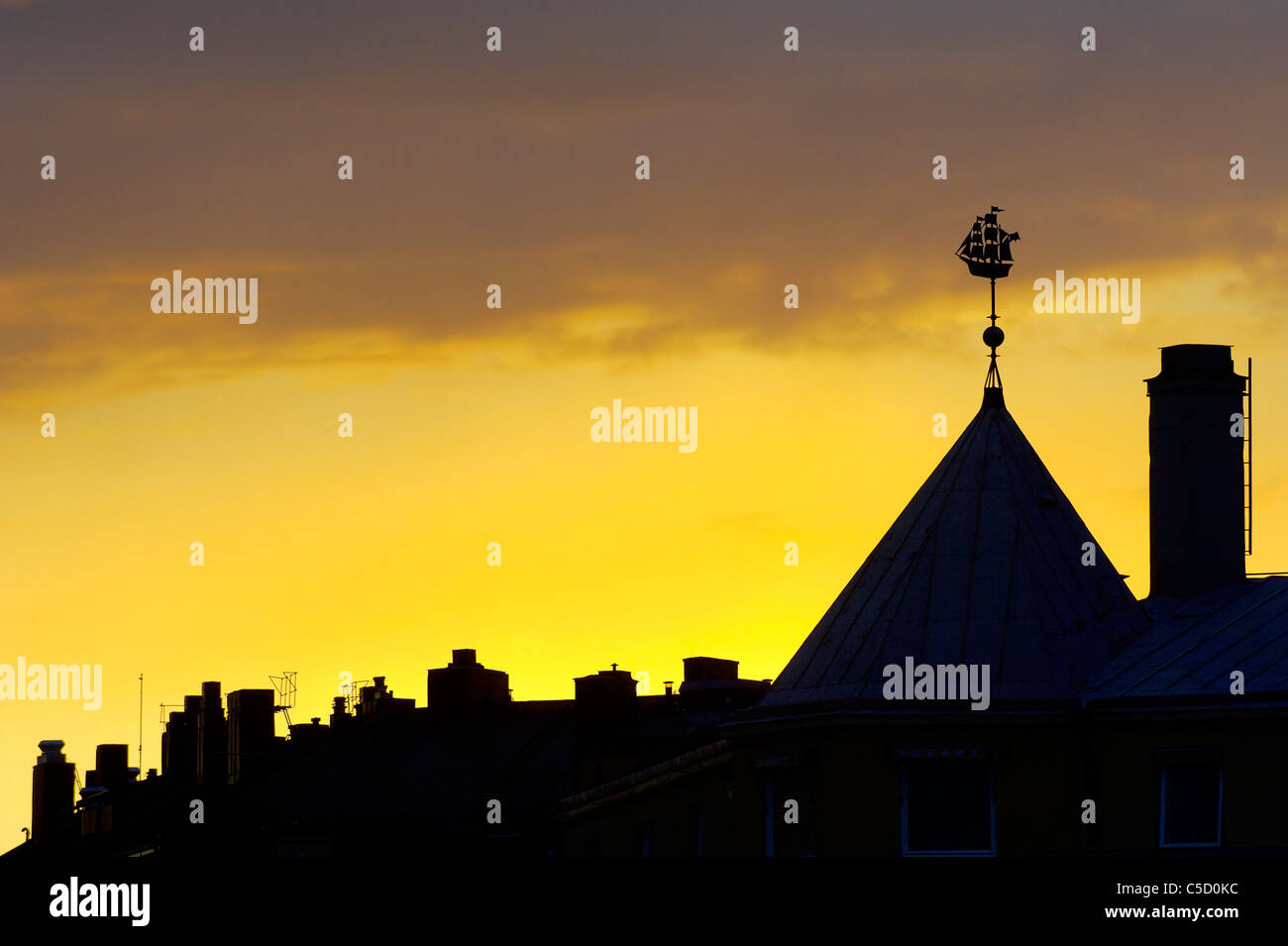 High section of silhouette buildings against yellow sky at sunset, Stockholm, Sweden - Stock Image