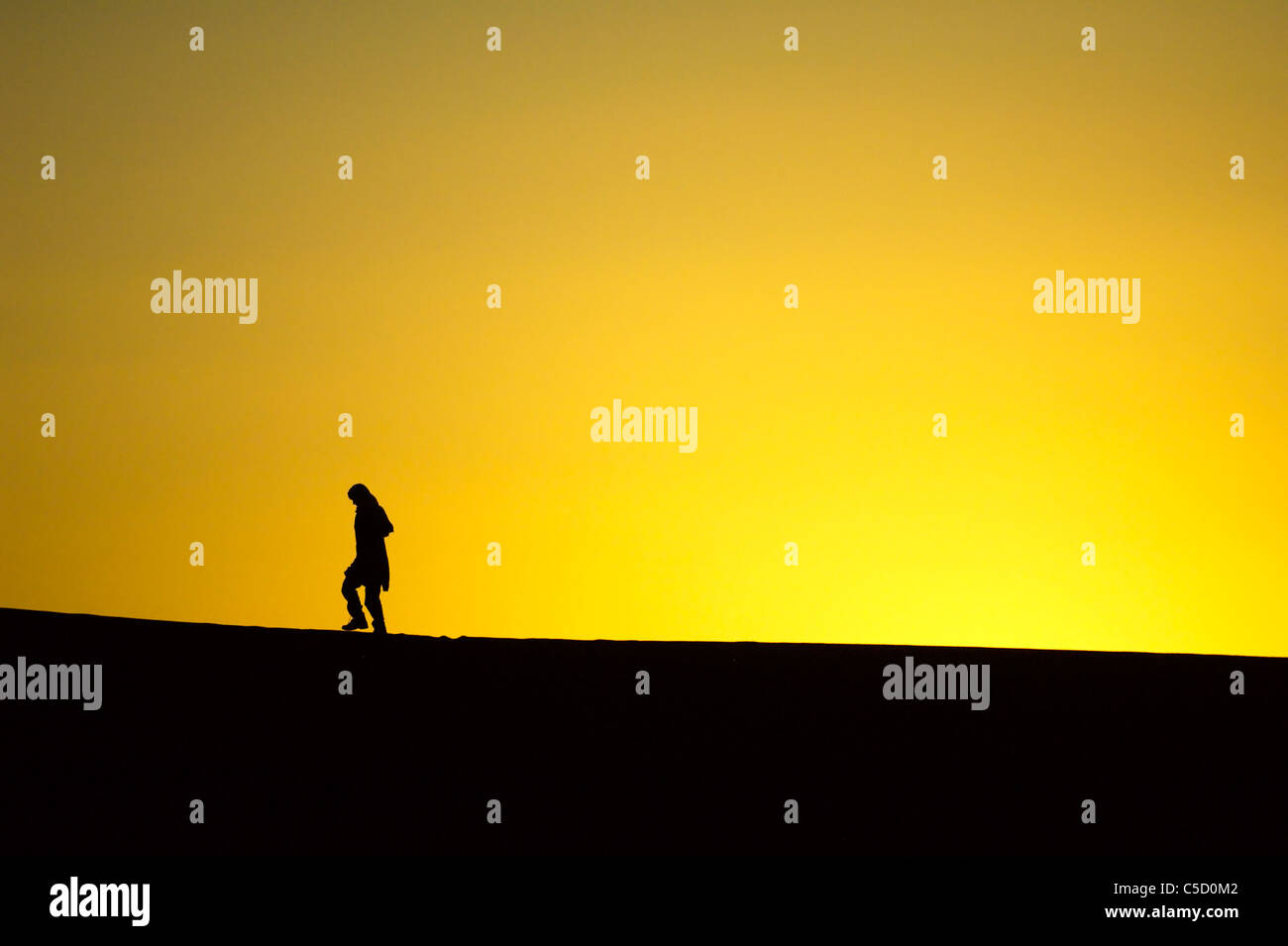 Side view of a silhouette woman against yellow background in Africa - Stock Image