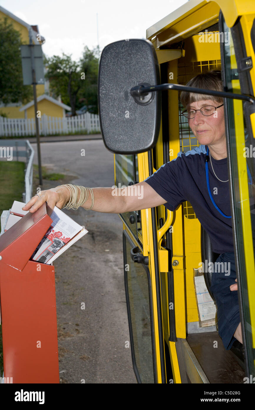 Female mail carrier dropping letters in mailbox with electric car - Stock Image