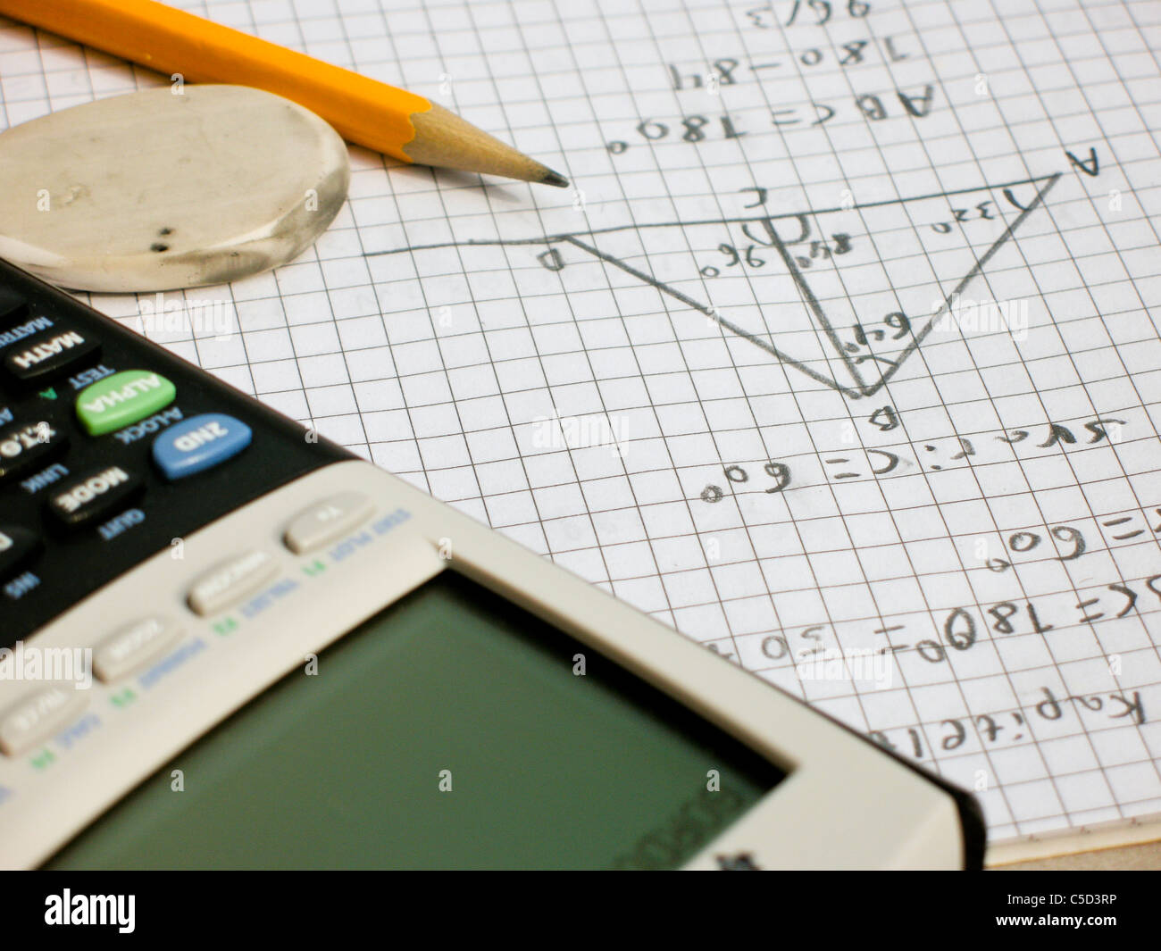 Close-up of a cropped calculator with pencil and digits in book - Stock Image