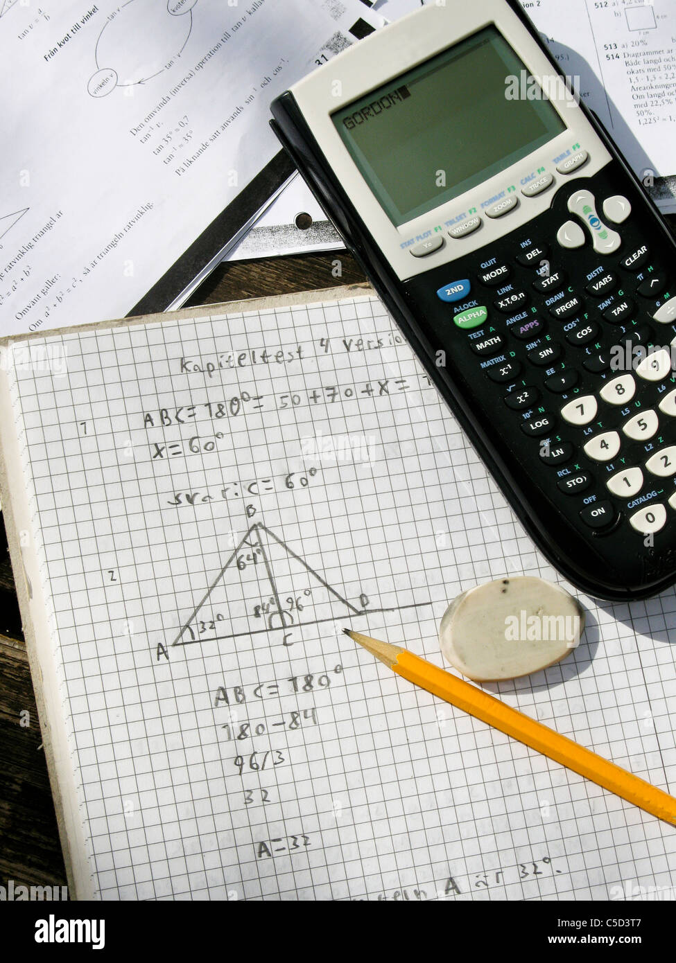 Close-up of a calculator with pencil and digits in book - Stock Image