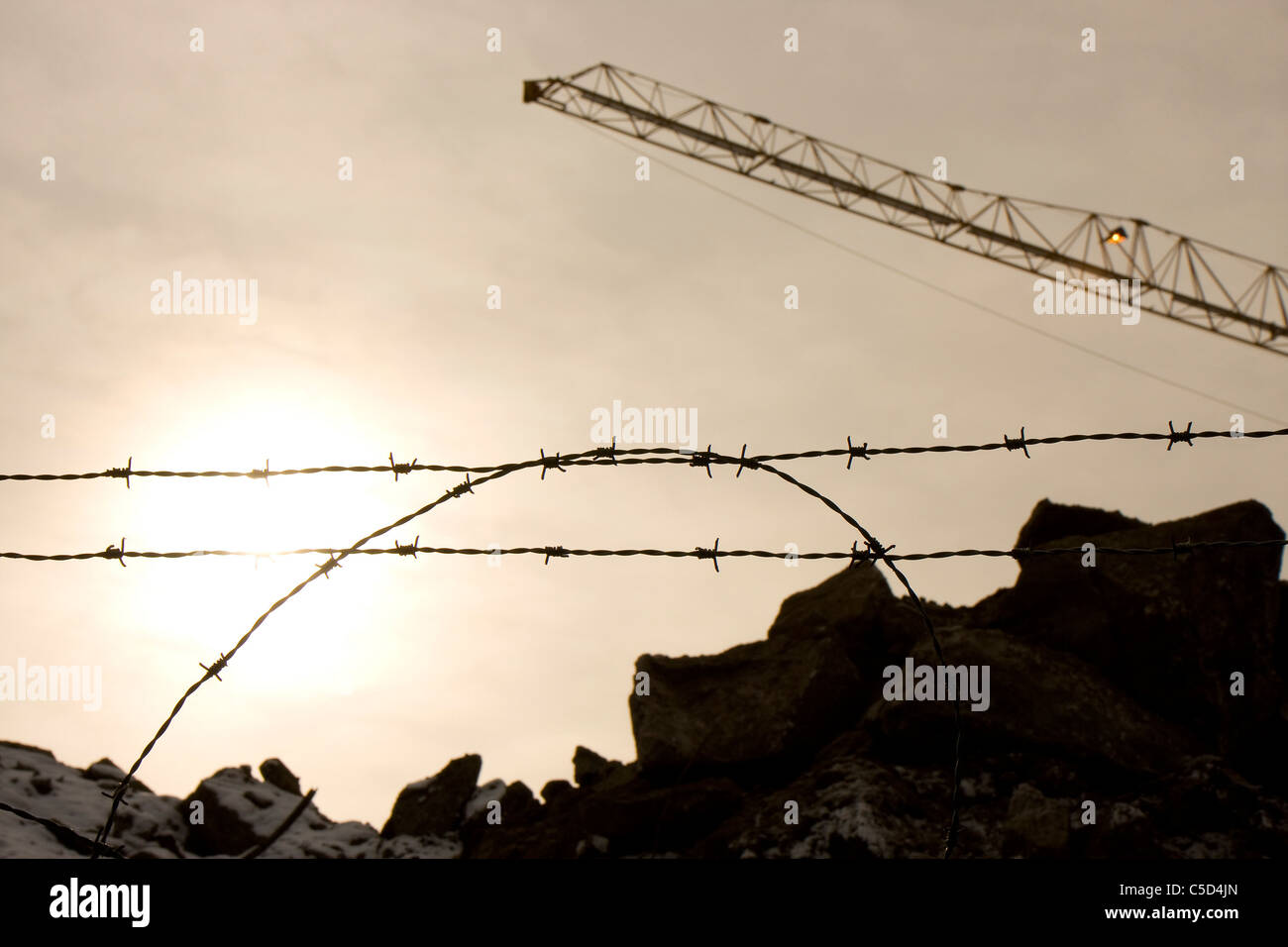 Close-up of barbed wire fence with rocks and crane against clear sky ...