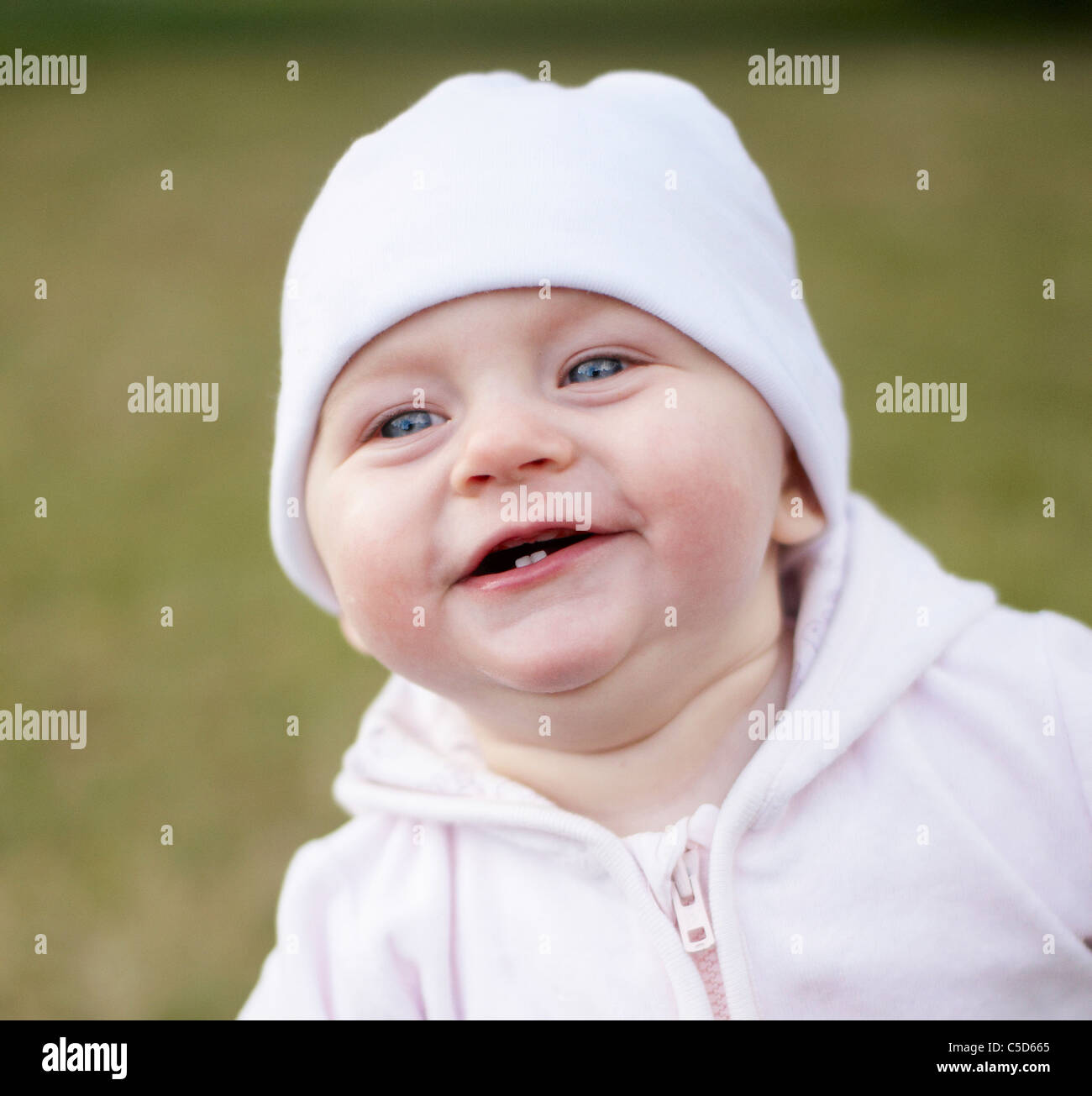 f08d94c79f2 Close-up of a cute baby with white beanie against blurred background ...