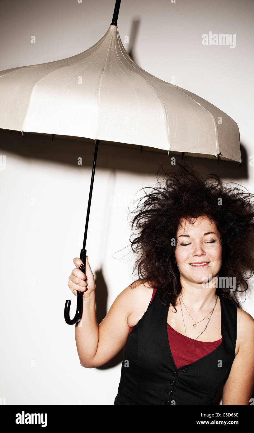 Young woman with tousled black hair and eyes closed holding an umbrella over white background - Stock Image