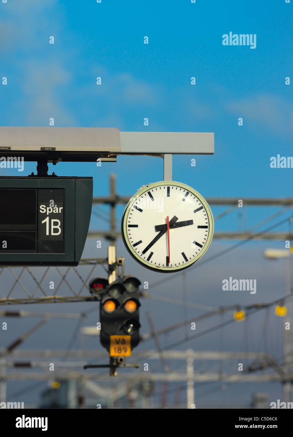 Close-up of a clock at the train station against blue sky - Stock Image