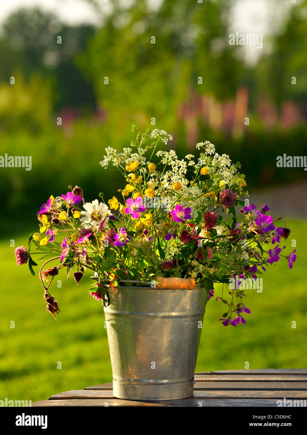 Close Up Of Beautiful Midsummer Flowers In Bucket Against Blurred