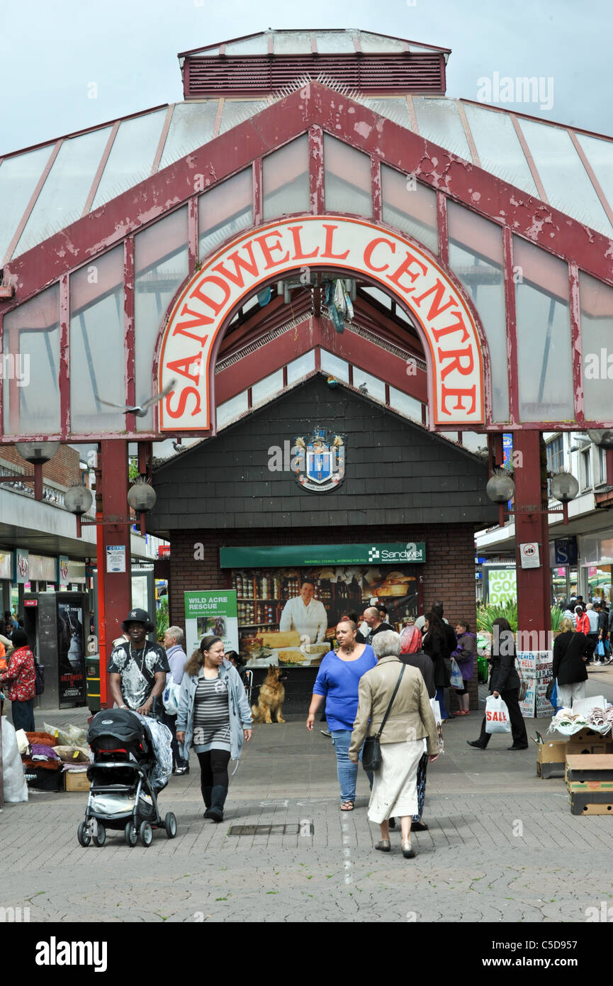 Shoppers walking under a shabby West Bromwich Kings Square shopping arcade atrium with large sign saying Sandwell - Stock Image