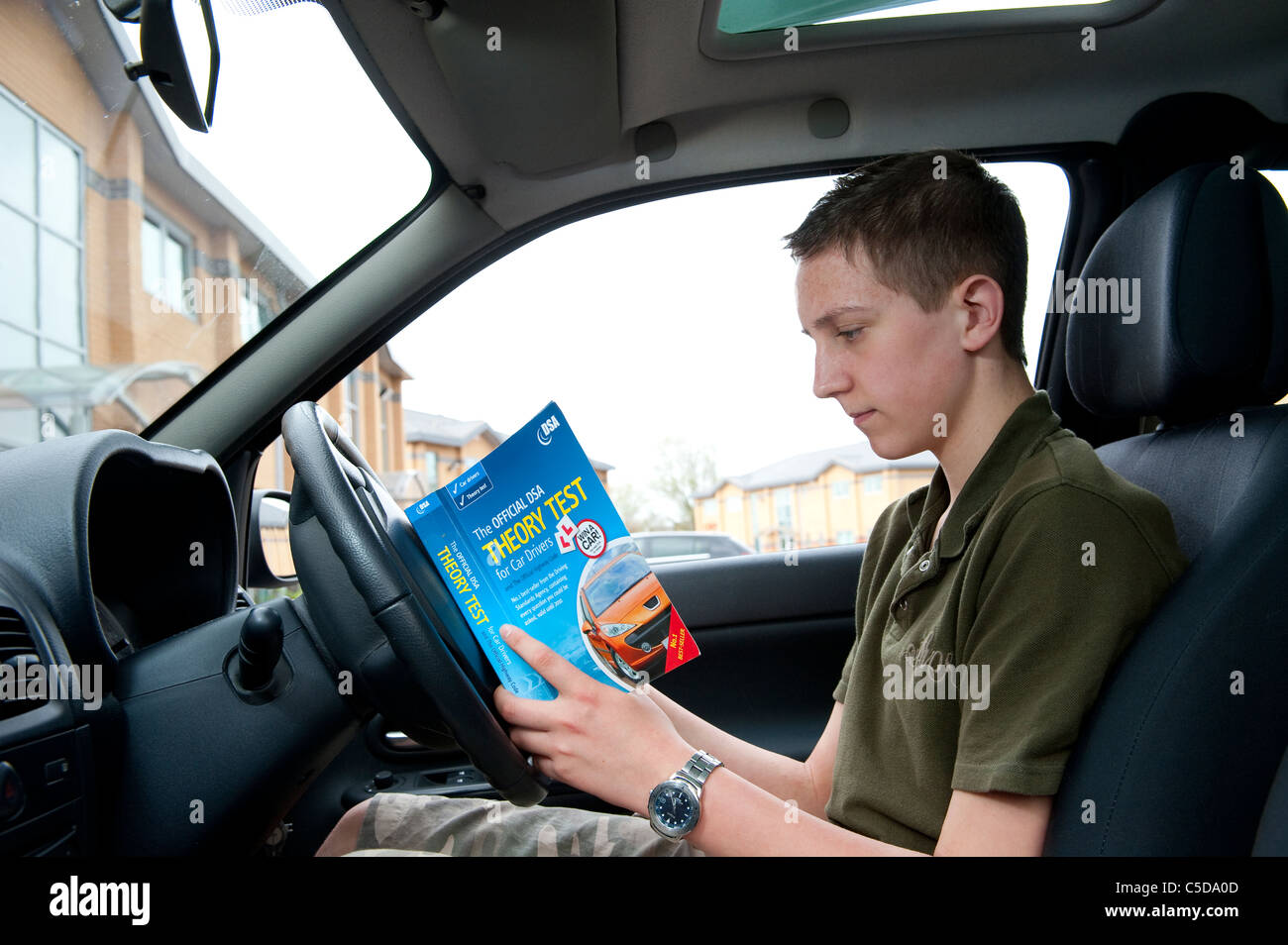 Teenage boy studying the official dsa theory test handbook before a driving lesson. - Stock Image
