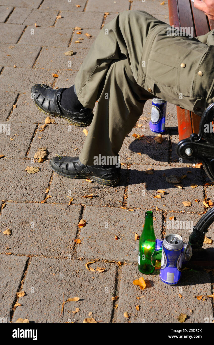 Beer tins and bottle besides a cropped person sitting on bench with legs crossed at knee - Stock Image