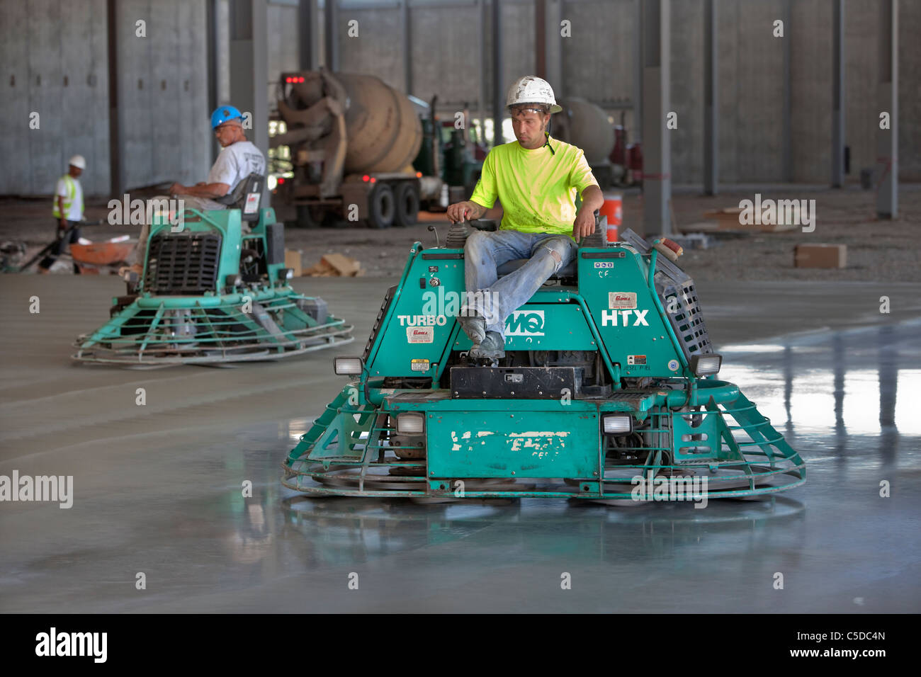 Cement Polishers Riding Power Trowels over freshly poured concrete can smooth the surface to a glass-like finish! - Stock Image