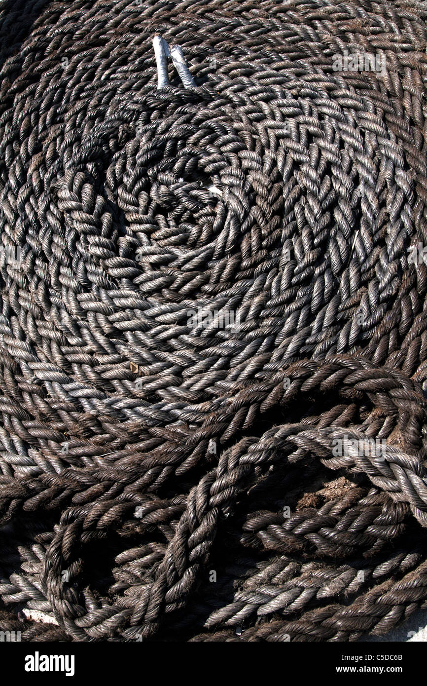 A coil of old rope lying on a quayside. - Stock Image