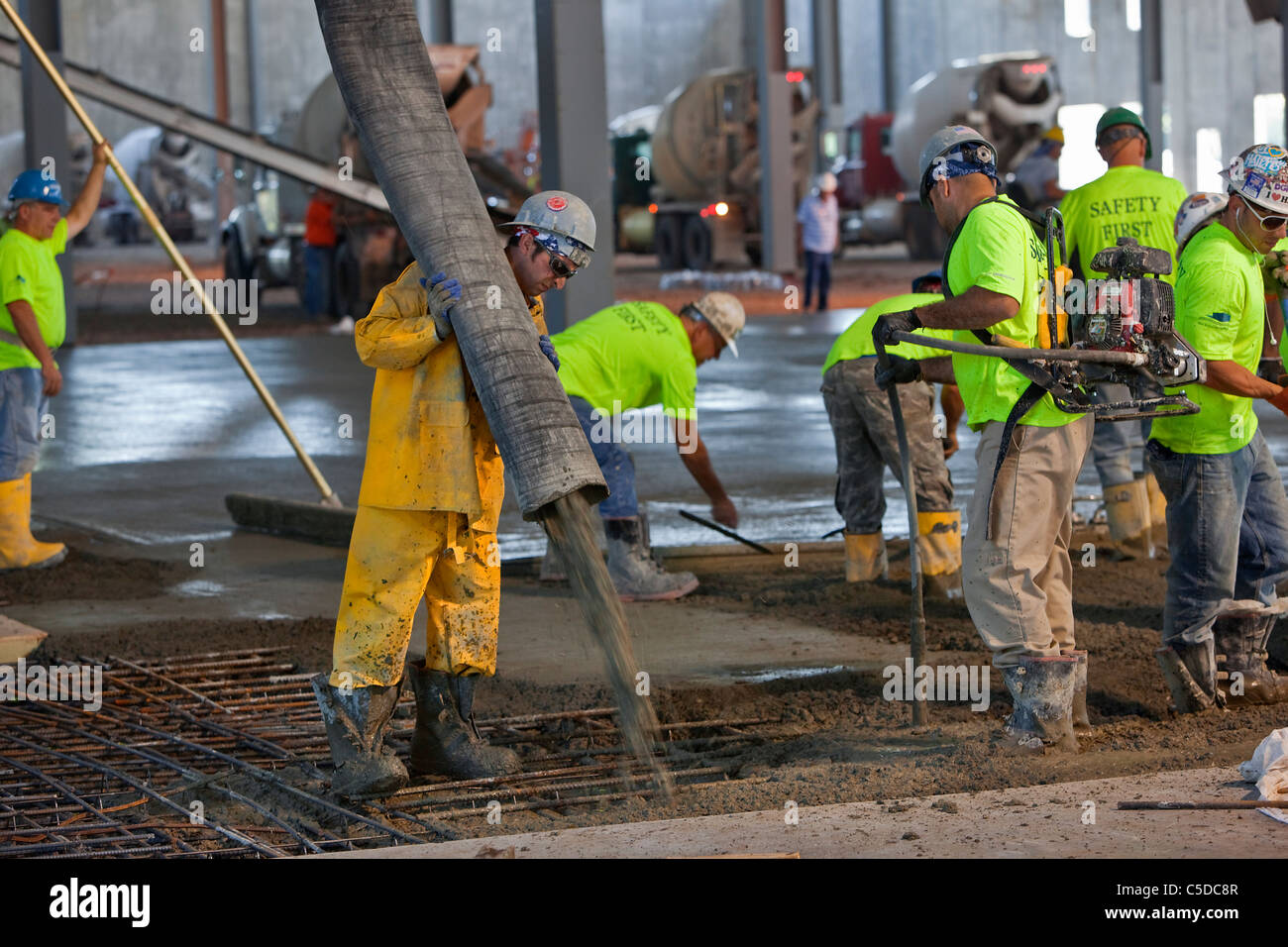 Concrete Pour over Rebar (reinforcing steel, reinforcement steel) - Stock Image