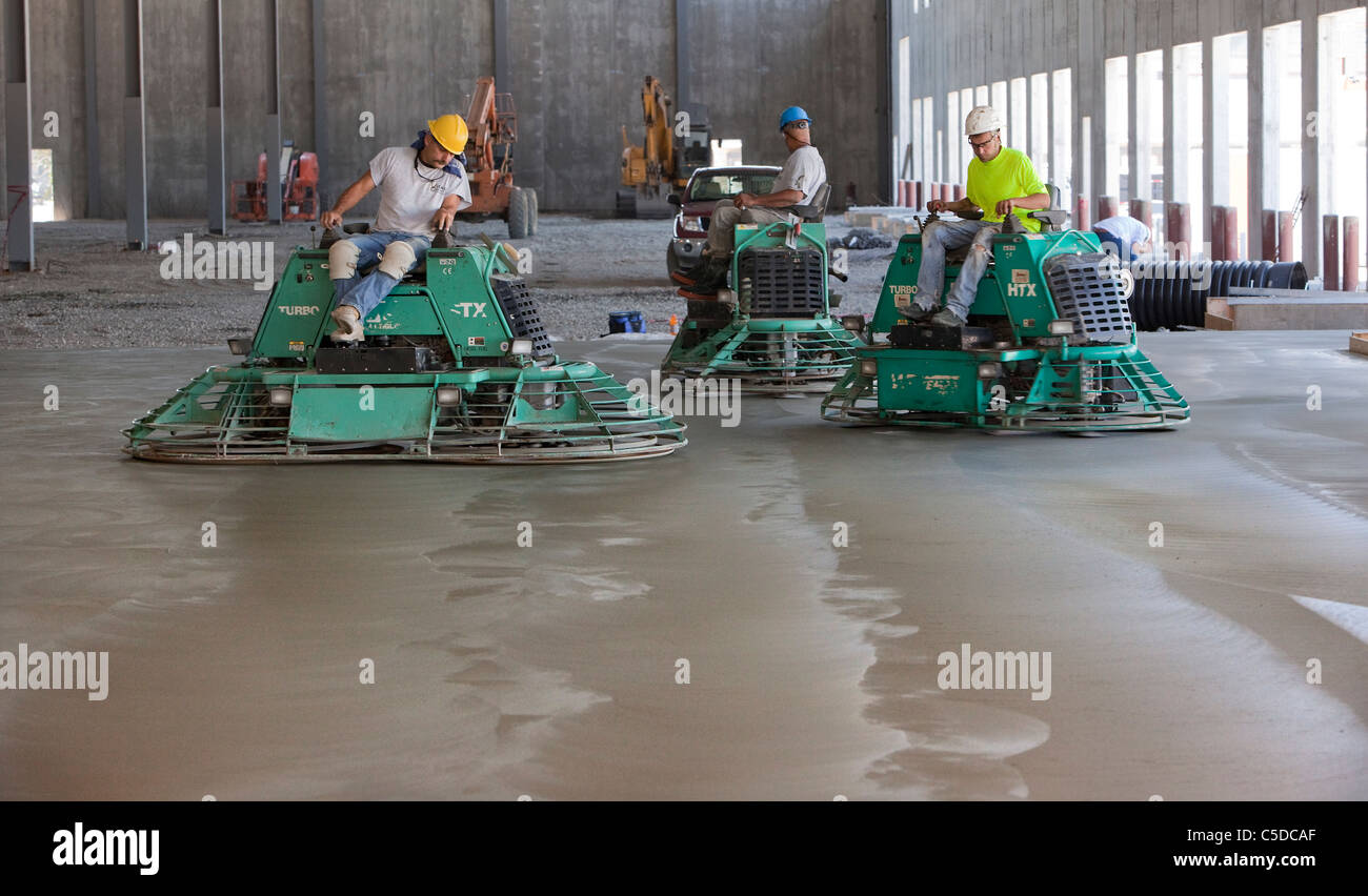 Cement Polishers Riding Power Trowels over freshly poured