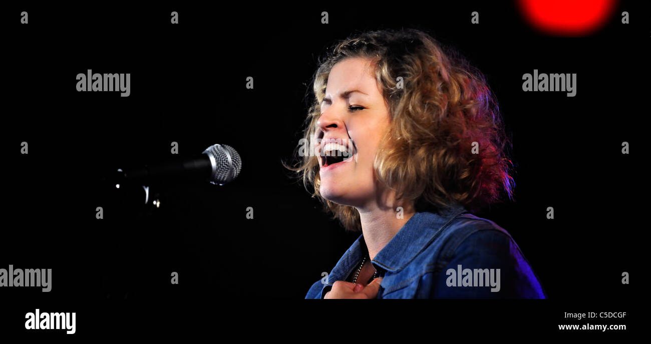 Panoramic shot of a female singer singing into microphone against dark background - Stock Image