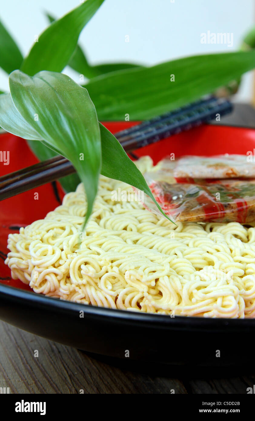 Instant  Asian noodle fast food with chopsticks in a red cup - Stock Image