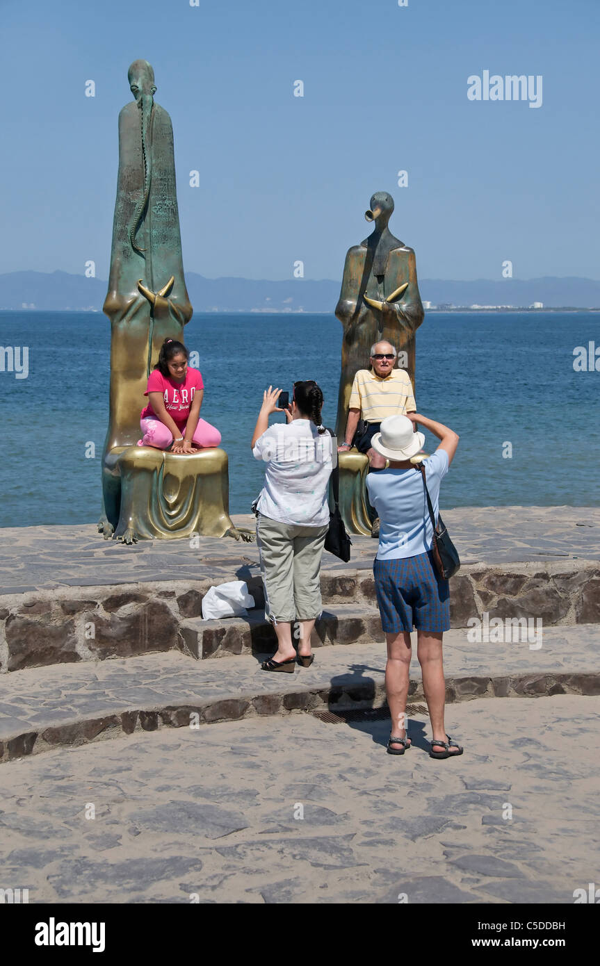 Tourists pose by sitting on the high-backed abstract public sculptures on the malecon in Puerto Vallarta, Mexico. - Stock Image