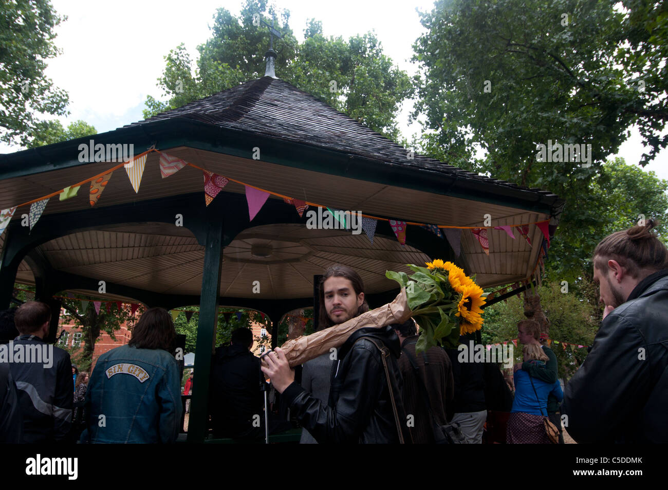 Arnold Circus Shoreditch, London July 2011. Man with bunch of sunflowers in front of bandstand. - Stock Image