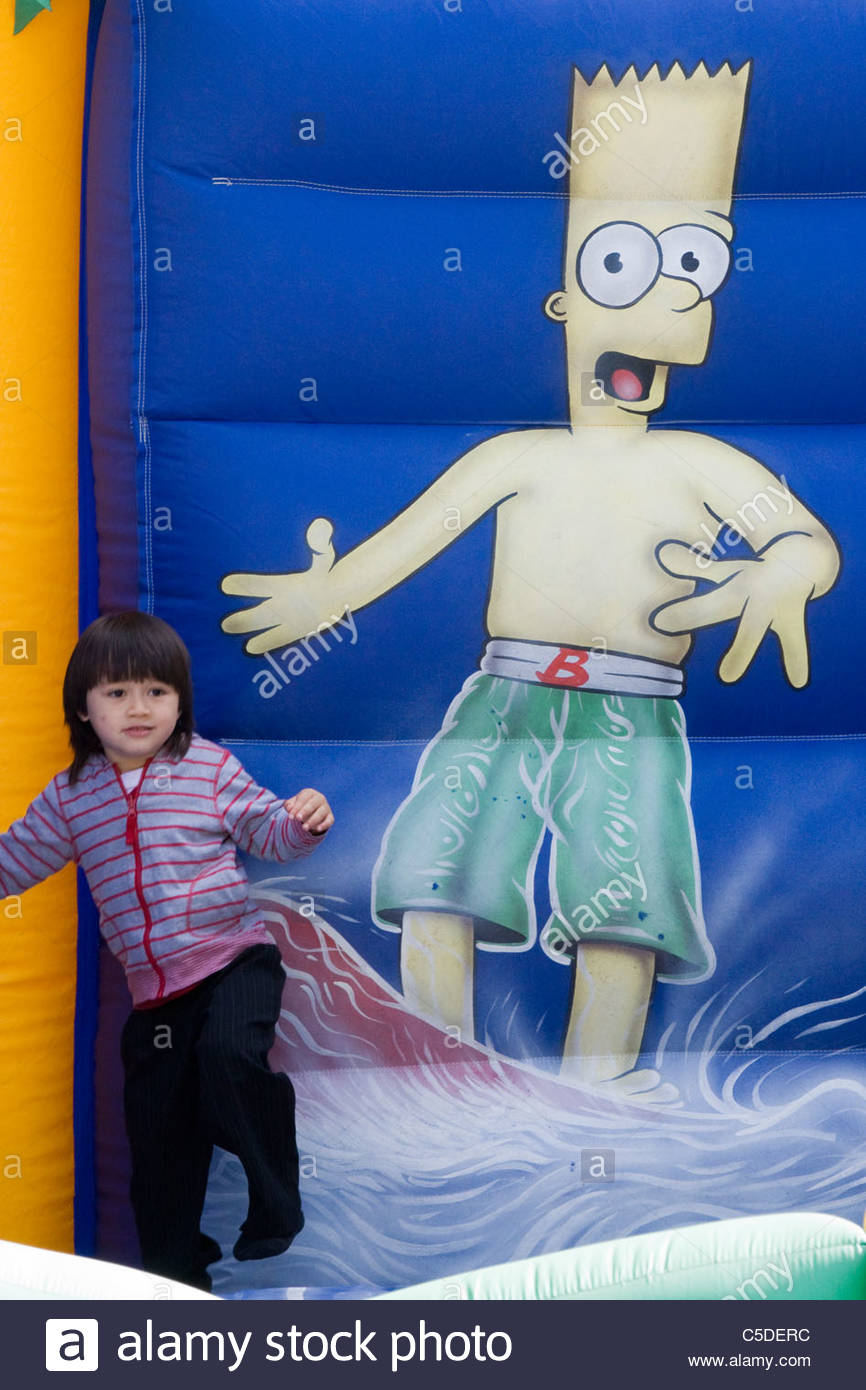 A Bart Simpson inflatable jumping castle with a Thai boy playing on it - Stock Image