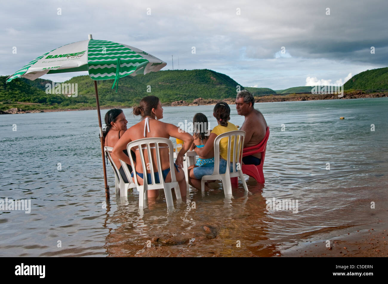 Having a meal  at table and chairs in the river  to keep cool - Stock Image