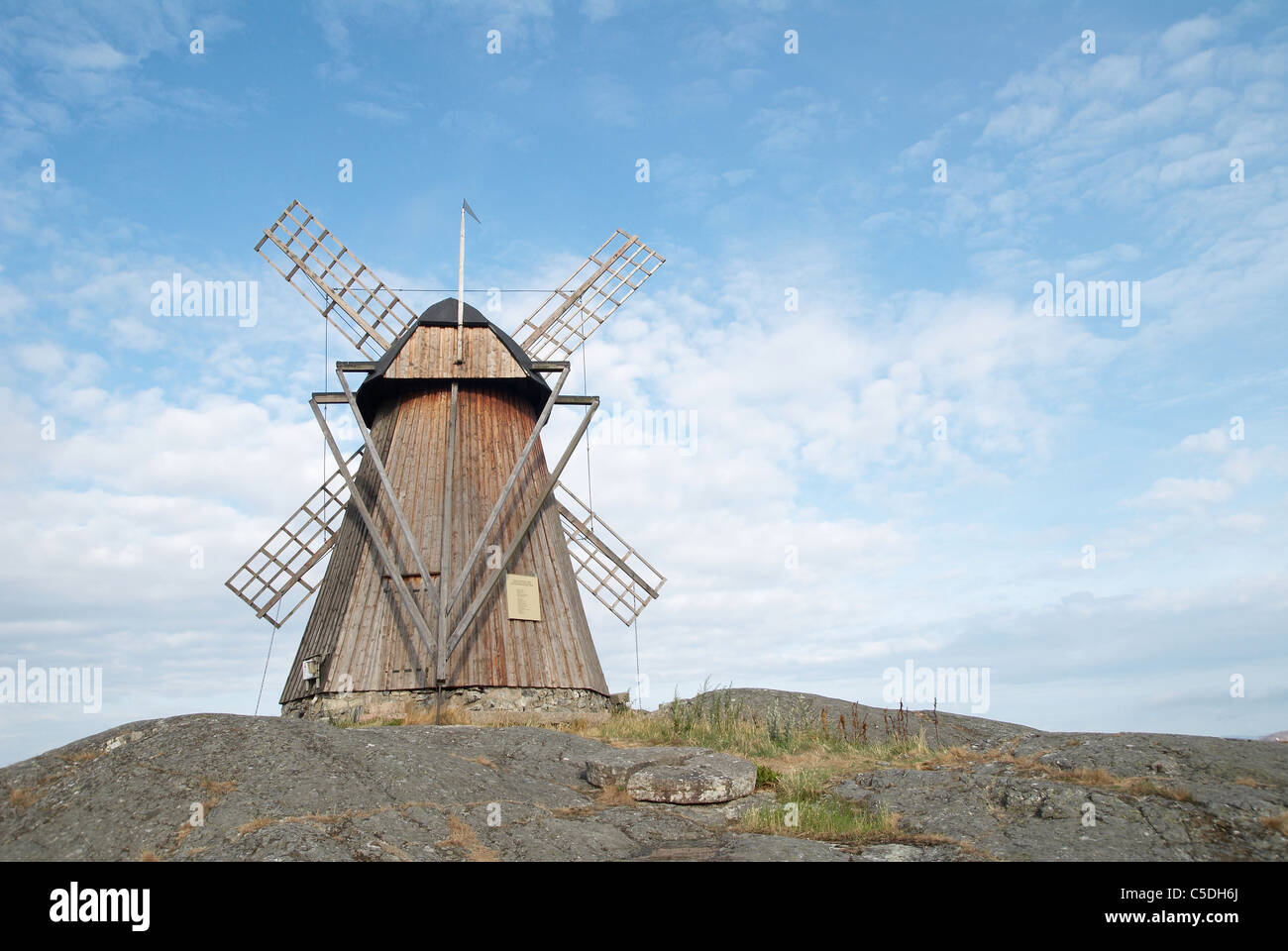 Low angle view of an old wooden windmill against blue sky and clouds - Stock Image