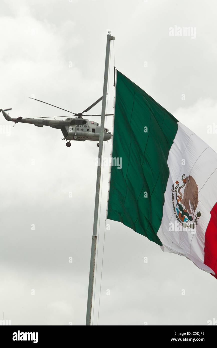A Mexican Marine military helicopter patrols the Rio Grande River as it flies past a large Mexican flag at the U.S. - Stock Image